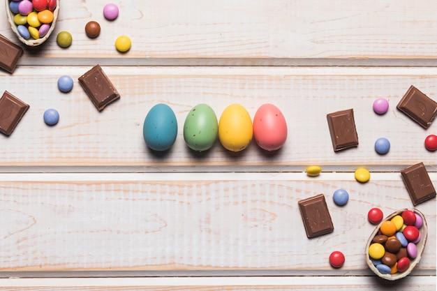Kleurrijke paaseieren met chocolade en edelstenen op houten bureau