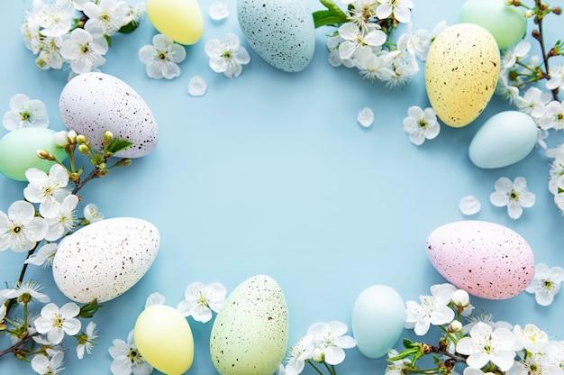 Kleurrijke paaseieren met lentebloesem flowersover blauwe achtergrond. gekleurde ei vakantie grens.