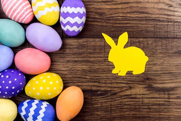 Kleurrijke paaseieren met silhouet van konijn op houten achtergrond