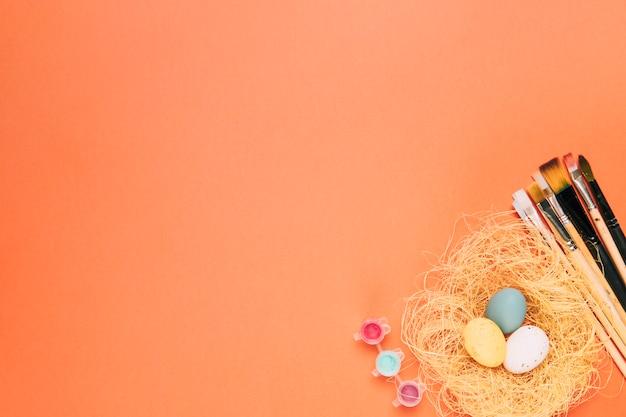 Kleurrijke paaseieren op het nest met verfborstels tegen een oranje achtergrond