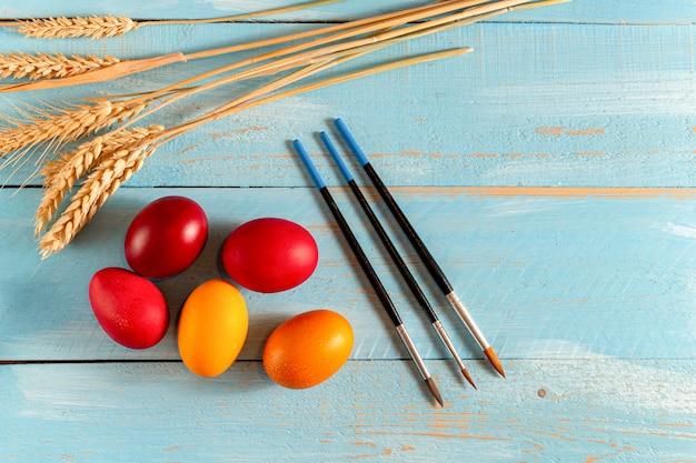 Kleurrijke paaseieren, oren van graan en penselen