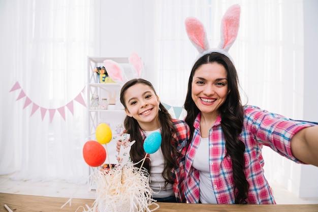 Kleurrijke paaseieren voor moeder en dochter die selfie thuis nemen