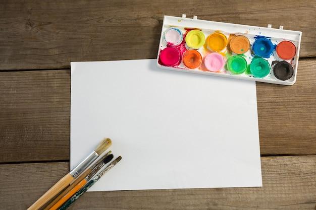 Kleurrijke palet verfborstels gerangschikt en blanco papier op houten oppervlak