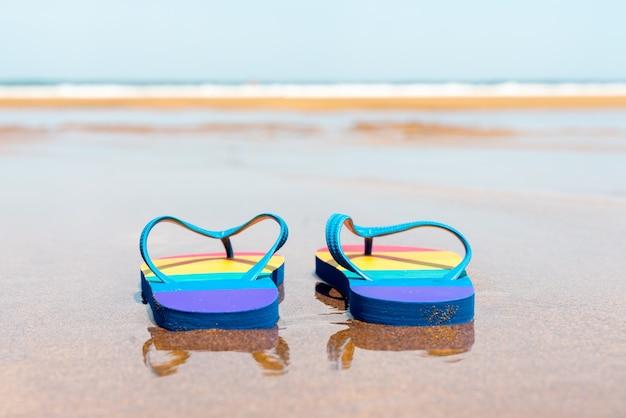 Kleurrijke pantoffels op het strand op een zomerdag teenslippers met gay pride-vlag