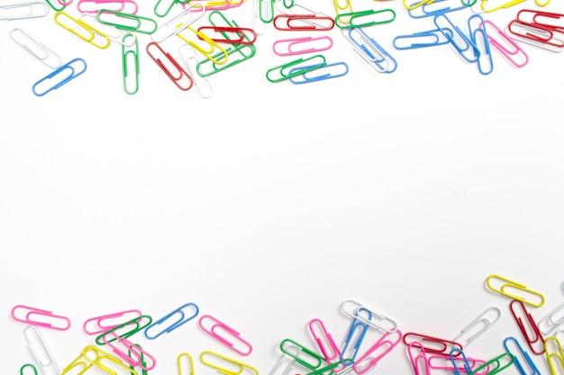 Kleurrijke paperclips geïsoleerd op wit met vrije ruimte in het midden.