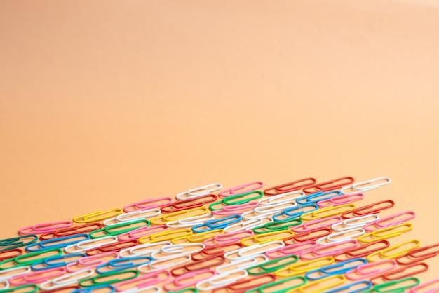 Kleurrijke paperclips op oranje achtergrond. terug naar school. verschillende kleuren draadpluggen zijn één type kantoormateriaal. copyspace