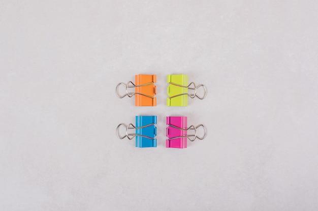 Kleurrijke paperclips op witte achtergrond.