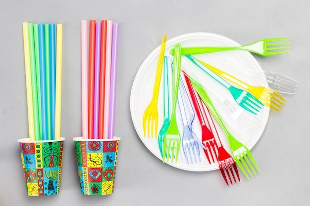 Kleurrijke papieren bekertjes en kleurrijke plastic rietjes voor drankjes. plat leggen