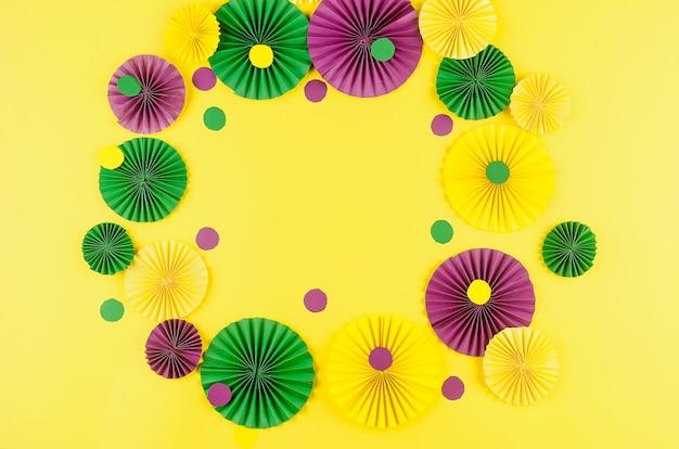 Kleurrijke papieren confetti, carnivalemasker en gekleurde serpentijn op een gele achtergrond