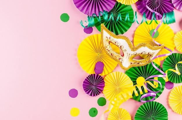 Kleurrijke papieren confetti, carnivalemasker en gekleurde serpentijn op een roze achtergrond