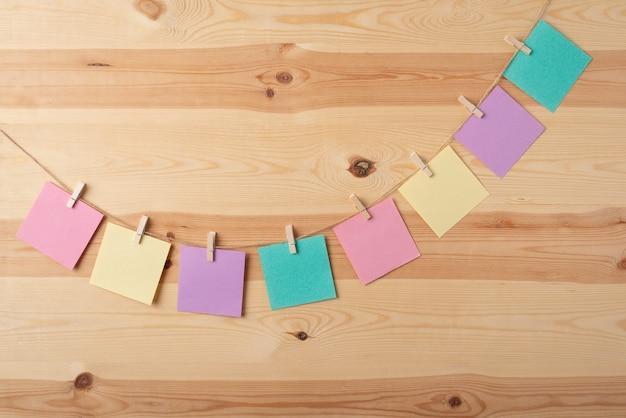 Kleurrijke papieren notities op een draad tegen houten tafel