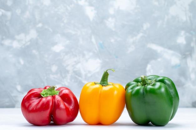 Kleurrijke paprika's bekleed op wit bureau, plantaardig kruid warm voedsel maaltijd ingrediënt product