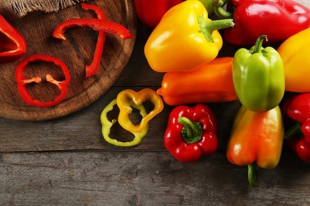 Kleurrijke paprika's op rustieke houten tafel, close-up