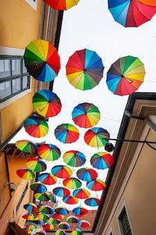 Kleurrijke paraplu'sachtergrond met blauwe lucht in de stadsstraatdecoratie