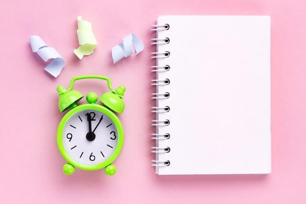 Kleurrijke partij streamers en een wekker op een roze achtergrond
