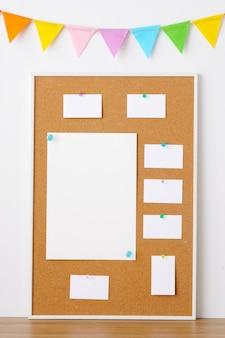 Kleurrijke partijvlaggen die op cork raad met lege notadocumenten hangen