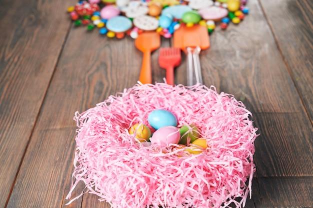 Kleurrijke pasen-koekjes en nest met eieren.