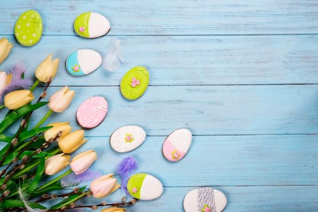 Kleurrijke pasen-koekjes en tulpen op blauwe houten achtergrond