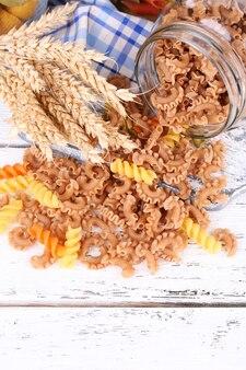 Kleurrijke pasta in glazen potten op houten oppervlak