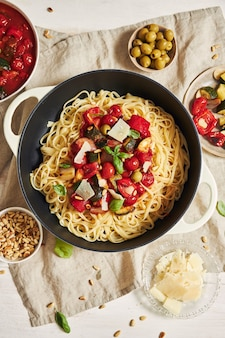 Kleurrijke pasta met groenten en ingrediënten op een witte tafel