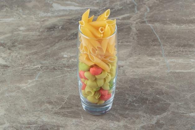 Kleurrijke pasta met schelp en penne in glas