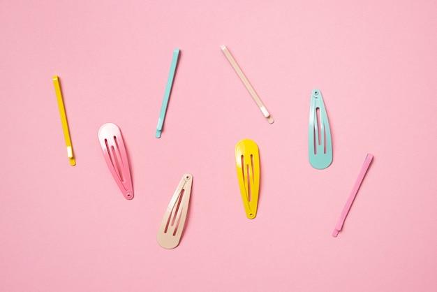 Kleurrijke pastel accessoires haarspeld op roze achtergrond close-up trendy modern uit het verleden