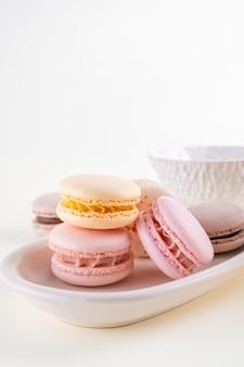 Kleurrijke pastel franse bitterkoekjes of macarons met kopjes op witte achtergrond