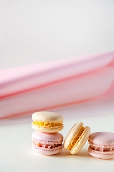 Kleurrijke pastel franse bitterkoekjes of macarons op witte en roze achtergrond