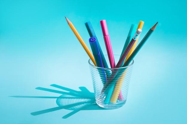 Kleurrijke pen en potlood in glas met lange schaduw op pastel achtergrond
