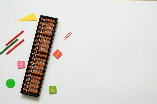 Kleurrijke pennen en potloden, cijfers, telraamscores op wit