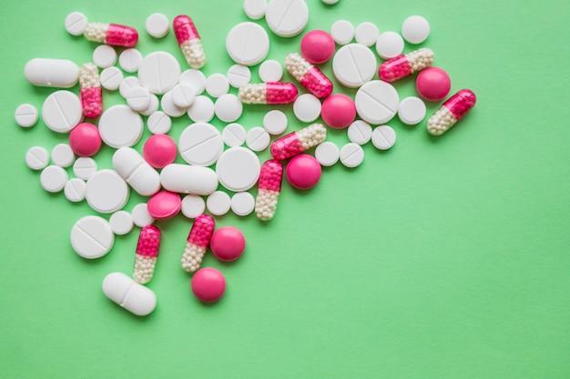 Kleurrijke pillen en drugs in close-up. geassorteerde pillen en capsules in de geneeskunde. drugs van verschillende soorten en verschillende kleuren.