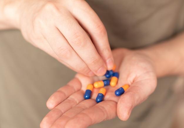 Kleurrijke pillen en medicijnen in de hand