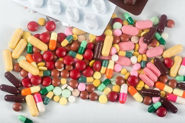 Kleurrijke pillen splatter op witte achtergrond. de verschillende tabletten en capsule heap mix-therapie drugs.