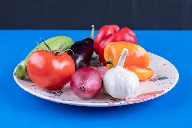 Kleurrijke plaat van verse rijpe groenten op blauwe ondergrond