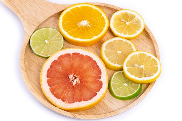 Kleurrijke plakjes citrusvruchten op een houten dienblad.