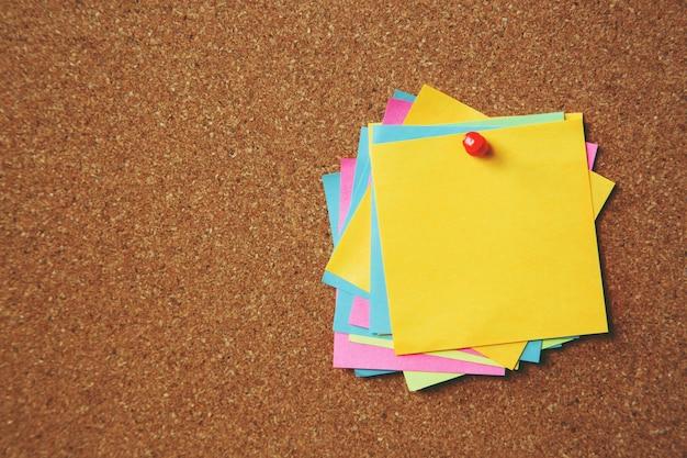 Kleurrijke plaknotities op het prikbord van kurk