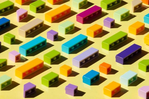 Kleurrijke plastic bakstenen op gele achtergrond.