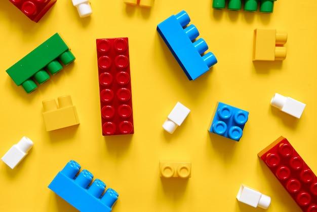 Kleurrijke plastic bouwstenen plat lag. geel kind ontwikkelt spel.