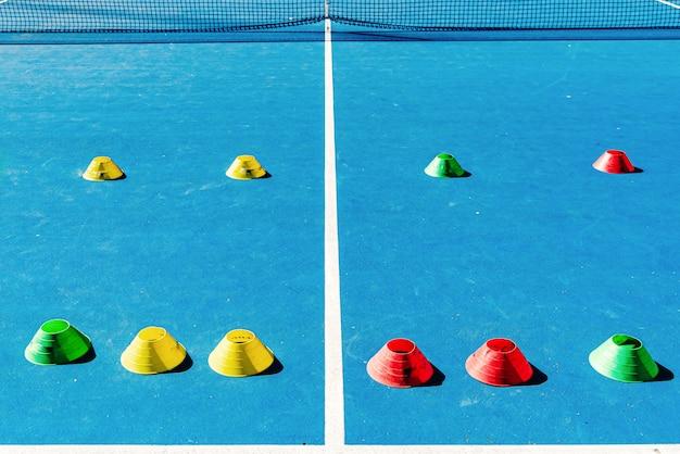 Kleurrijke plastic kegels op een blauwe cementtennisbaan met witte lijnen