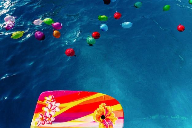 Kleurrijke plastic waterballonnen die in een pool drijven om op vakantie te spelen om af te koelen.