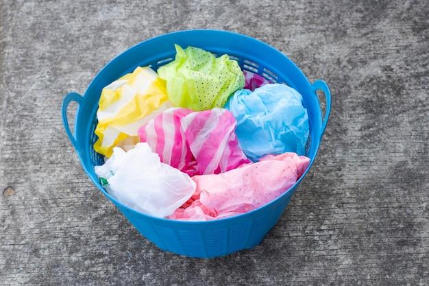 Kleurrijke plastic zakken in afvalmand op cementvloer