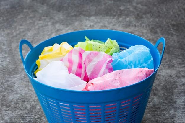 Kleurrijke plastic zakken in afvalmand op cementvloer.