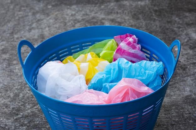 Kleurrijke plastic zakken in blauwe afvalmand op cementvloer