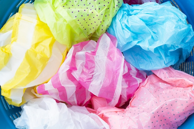 Kleurrijke plastic zakken in blauwe afvalmand