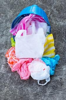 Kleurrijke plastic zakken met afvalmand op cementvloer