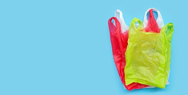 Kleurrijke plastic zakken op blauwe achtergrond.