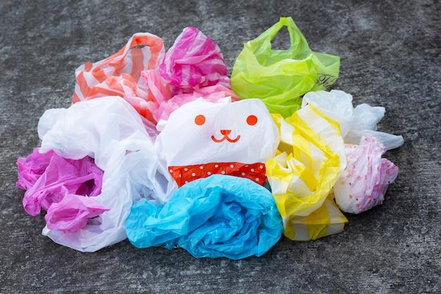 Kleurrijke plastic zakken op donkere cementvloer