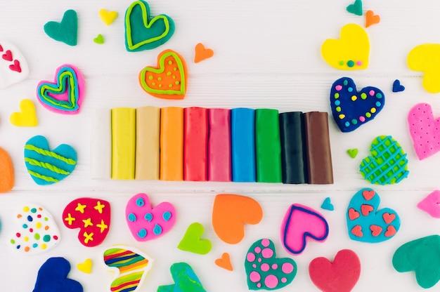 Kleurrijke plasticine keurige harten op witte houten