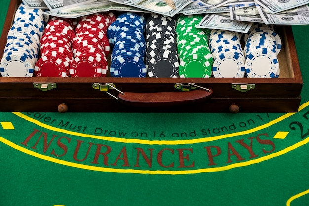 Kleurrijke pokerfiches op speeltafel met houten kist voor hen