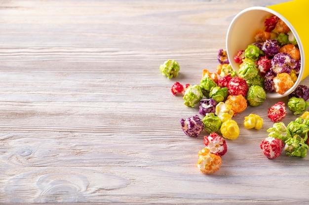 Kleurrijke popcorn in een kartonnen beker.